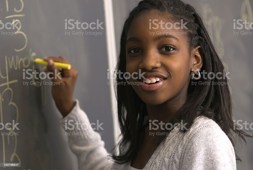 Student doing math on chalk board stock photo