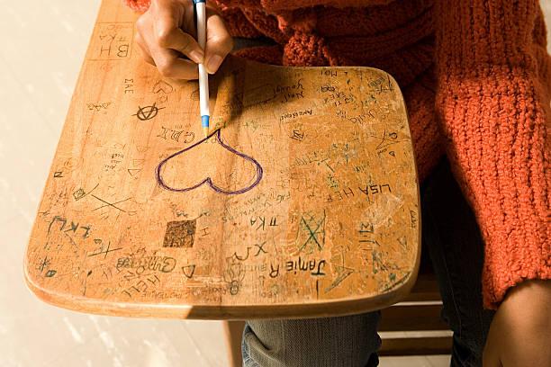 student zeichnen ein herz auf ihrem schreibtisch - sprüche für die liebe stock-fotos und bilder