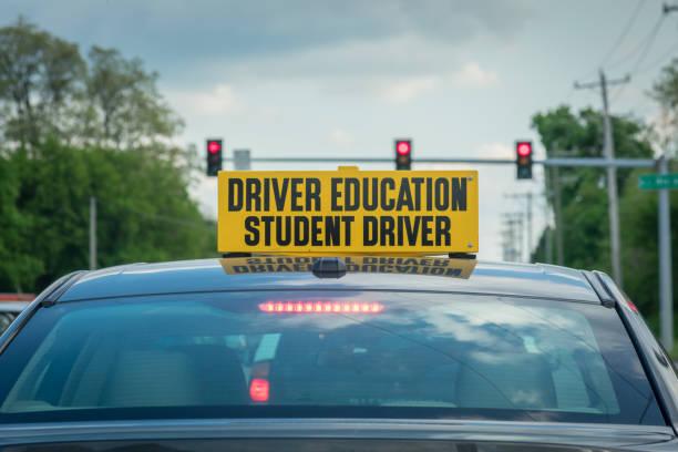 student-treiber melden sie an der spitze des autos an ampel - berufsfahrer stock-fotos und bilder