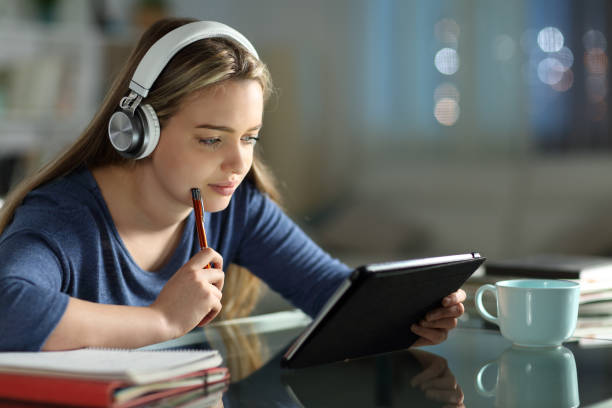 Student e-learning with tablet and headphones stock photo