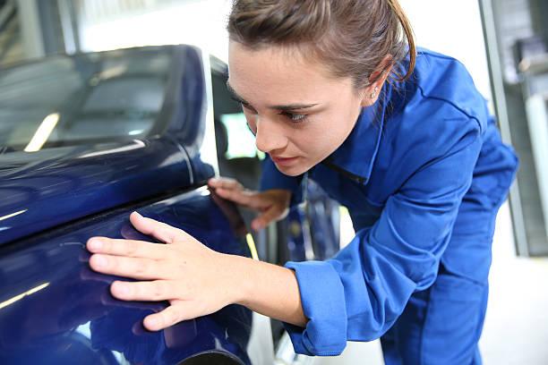 Student examining the bodywork of car in garage stock photo
