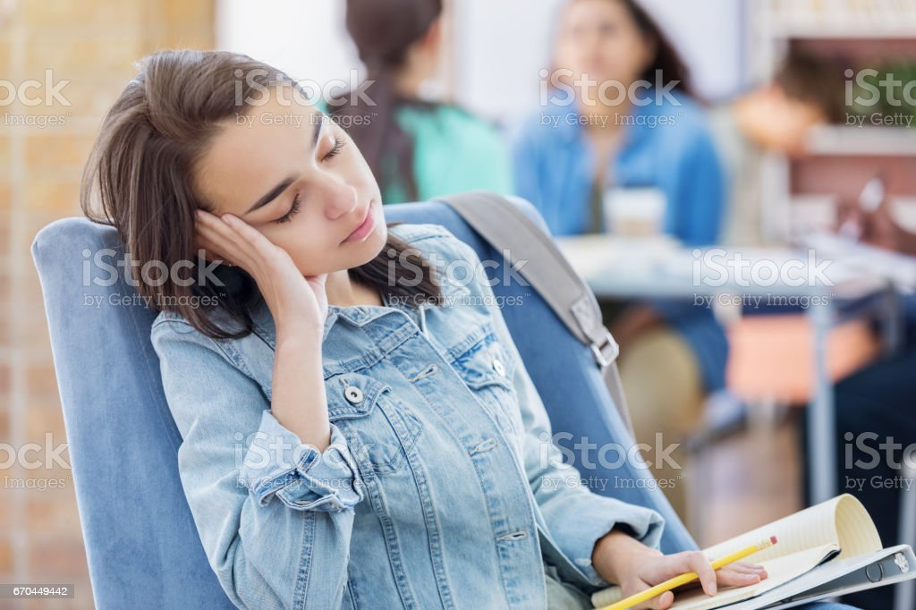 Student falls asleep while studying in the library stock photo