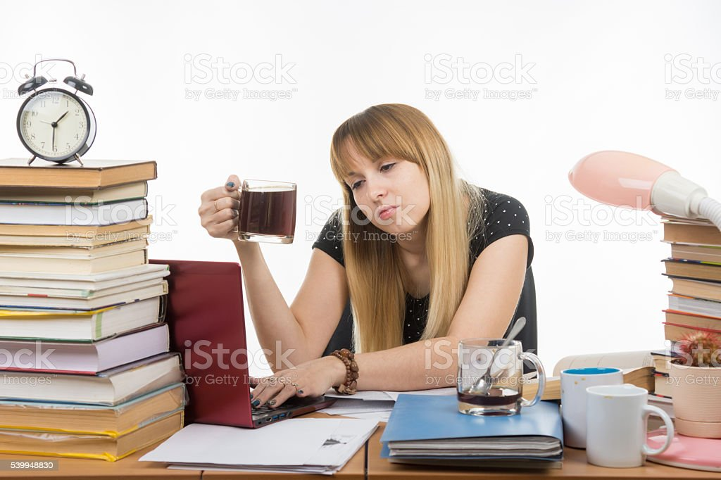 Student falls asleep with a mug of coffee in hand stock photo