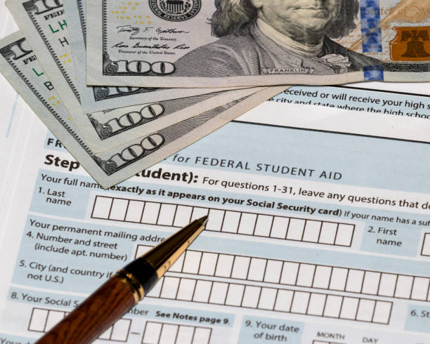 Student financial aid application forms for college tuition loans and grants with one-hundred dollar bills and ballpoint pen stock photo