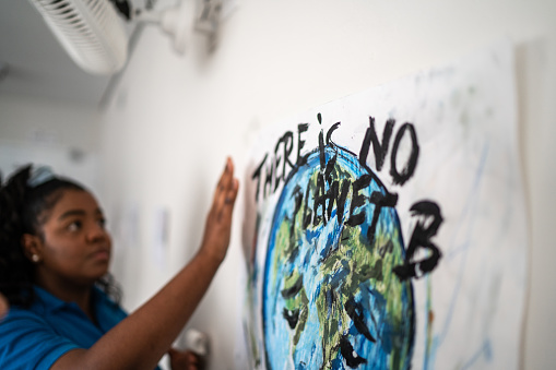 Student fixing in the wall a poster about environmental issues - There is no planet B
