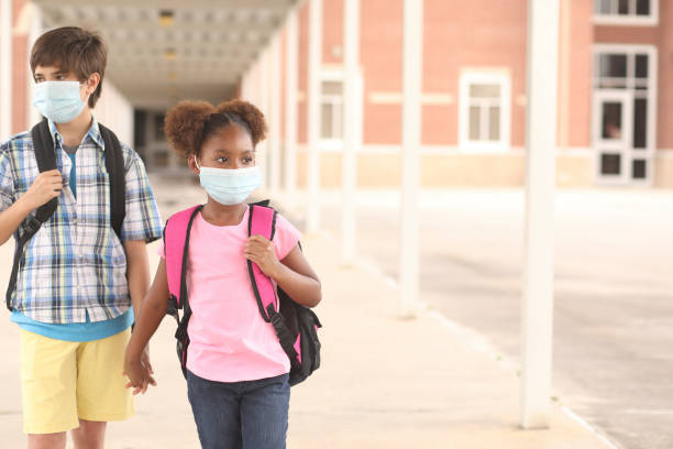 Student friends walk to class wearing masks for COVID-19. stock photo