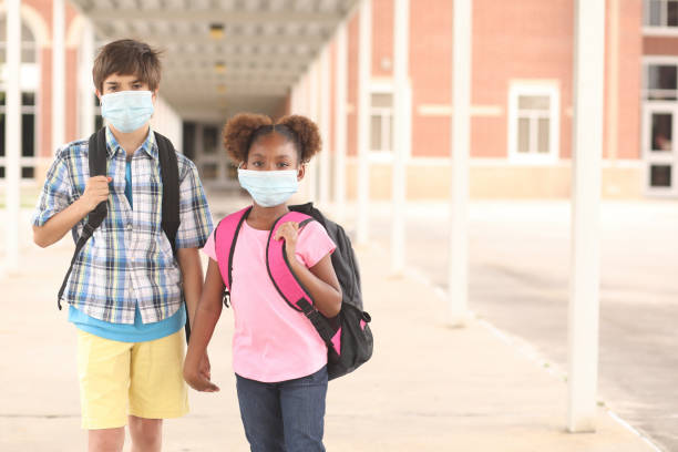 Student friends walk to class wearing masks for COVID-19. Back to school. Latin and African descent friends on school campus. They both wear a masks for COVID-19, Coronavirus protection.  They walk to class together.  School in background. covid stock pictures, royalty-free photos & images