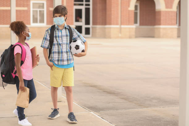 Student friends walk to class wearing masks for COVID-19. Back to school. Latin and African descent friends on school campus. They both wear a masks for COVID-19, Coronavirus protection.  They walk to class together.  School in background. covid-19 stock pictures, royalty-free photos & images
