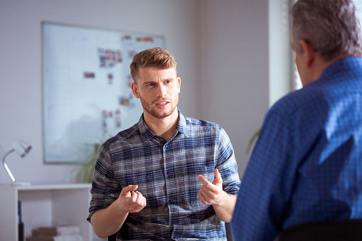Student Gesturing While Discussing With Therapist Stock Photo - Download Image Now