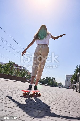 Student girl at pink skateboard. Local city traveller. Staycation lifestyle. Back view teenager. Copyspace. Place for text. Vertical banner for story. Extreme skate riding. Road to school