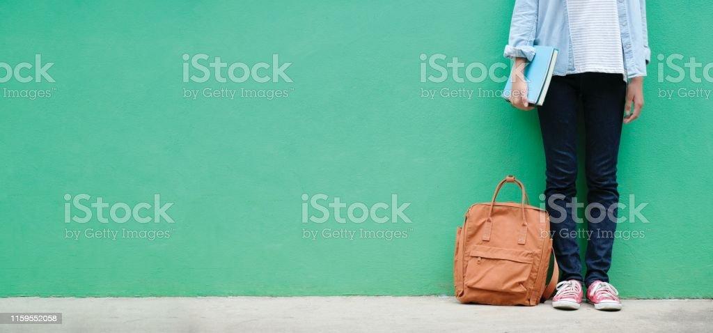 Schülerin Mädchen hält Bücher und Schultasche stehen über grüne Wand Hintergrund mit Kopierraum, Bildung Banner, zurück zum Schulkonzept - Lizenzfrei Akademisches Lernen Stock-Foto