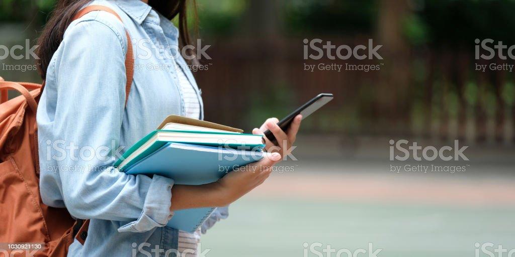 Chica estudiante con libros y smartphone mientras camina en el fondo del campus de escuela, educación, regresar al concepto de escuela foto de stock libre de derechos