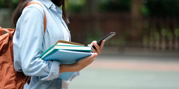 rapariga estudante segurando livros e smartphone enquanto caminhava em plano de campus de escola, educação, volta ao conceito de escola - universidade - fotografias e filmes do acervo