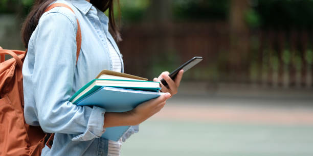 student girl holding books and smartphone while walking in school campus background, education, back to school concept - university stock pictures, royalty-free photos & images