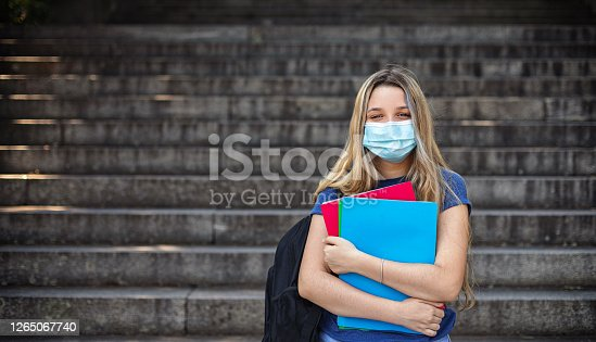 Student girl holding books while walking in school. She wears a mask for COVID-19, Coronavirus protection. Back to school concept