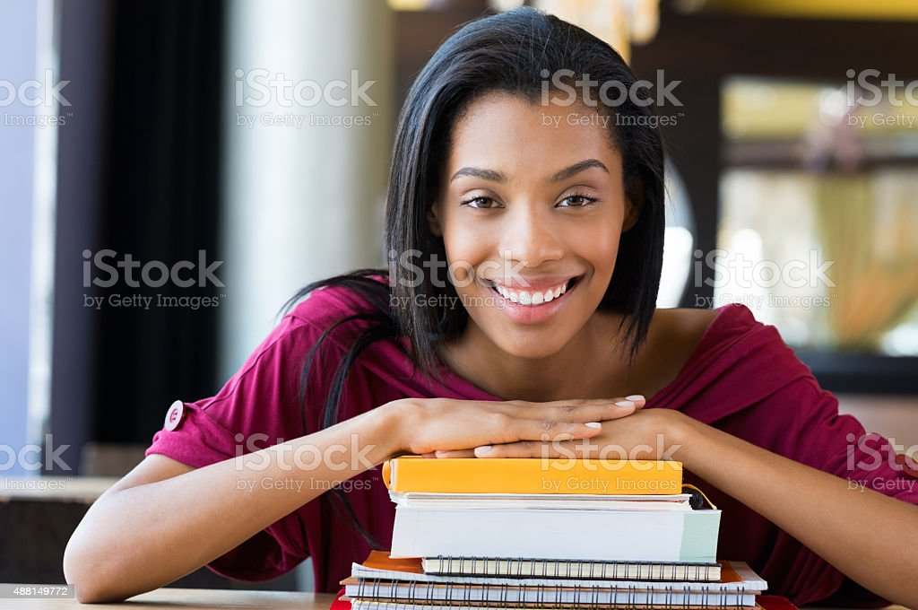 Student girl leans on stack of books stock photo