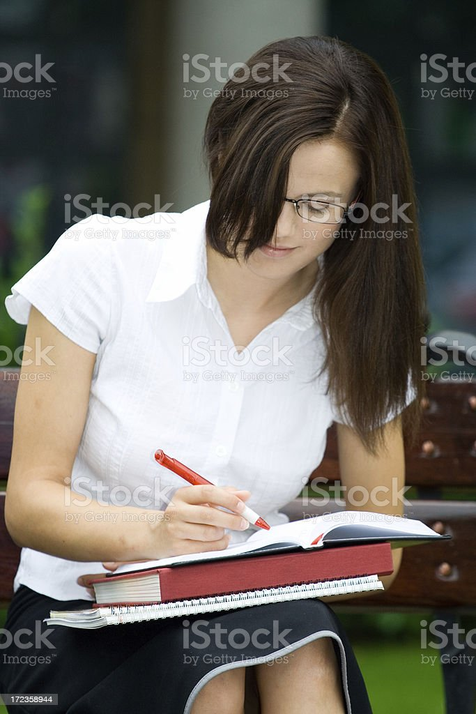 Student Girl on a park bench - learning royalty-free stock photo