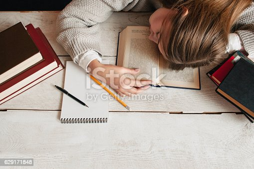 istock Student girl sleeping on desk with books flat lay 629171848