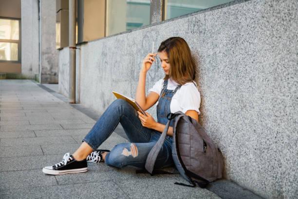 student girl studying sitting on the floor - esame maturità foto e immagini stock