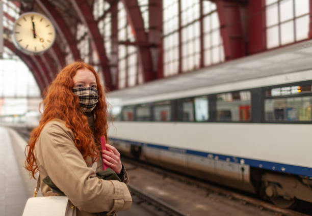 Student girl wearing a face mask stands at the tracks on the railway platform with clock behind her stock photo