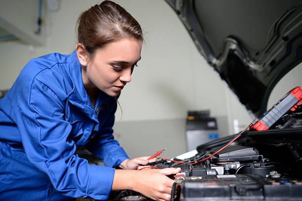 Student girl with blue dungarees repairing car stock photo