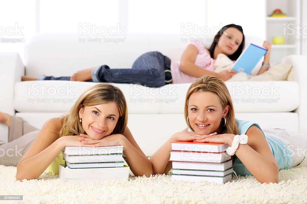 Student girls lying down with many books. royalty-free stock photo