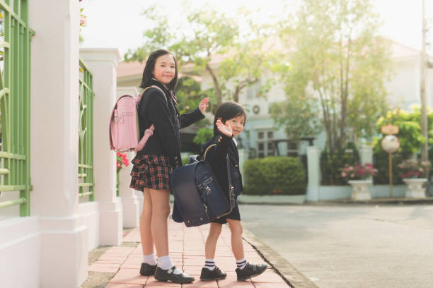 student going to school and waving goodbye stock photo