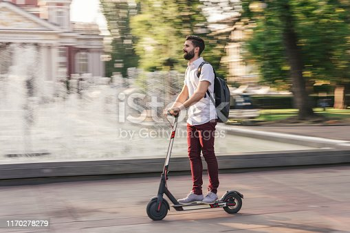 Confident young man riding electric scooter in the city