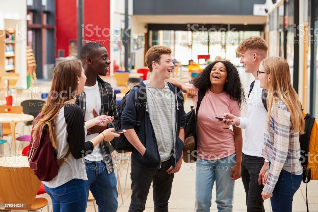 Student Group Socializing In Communal Area Of Busy College stock photo