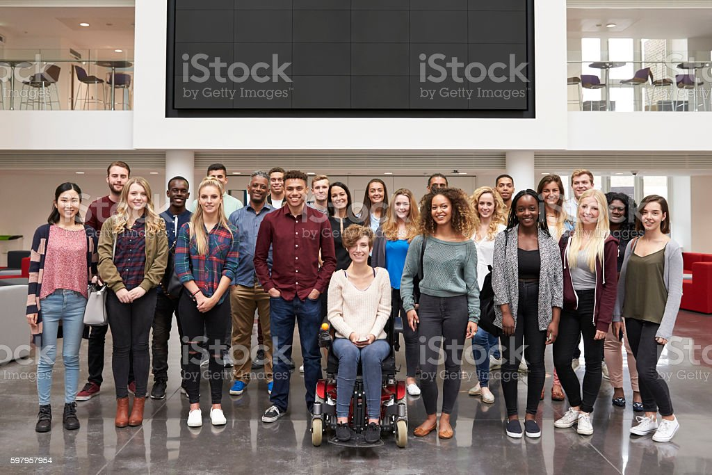 Student group standing in atrium under a big AV screen stock photo
