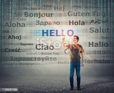 Student guy pointing index finger up choosing word hello with different translations. Multilingual teacher learning and speaking many languages. International communication concept.