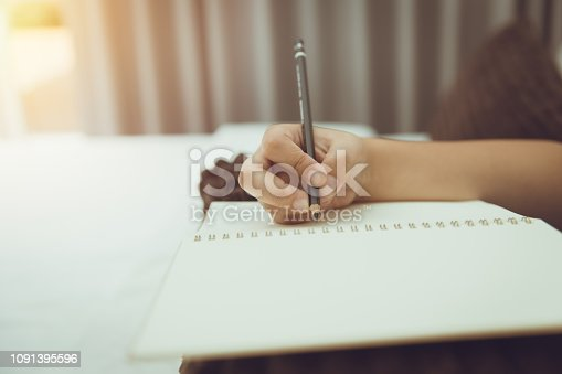 istock student hand hold pencil writing note blank book vintage colortone 1091395596