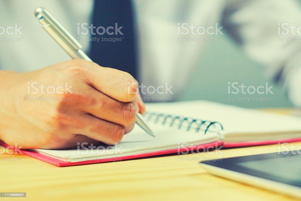 Student hand holding pen writing doing examination in university...