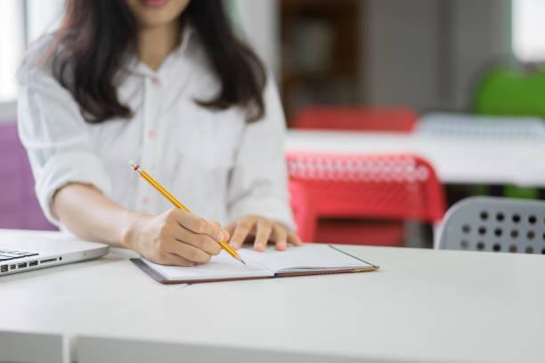 Student Hand mit Bleistift Schreiben der Prüfung an der Universität, Studenten in Uniform besuchen Prüfung Klassenzimmer Bildungsschule: Junge weibliche Unternehmen schreibt Informationen aus tragbaren Netzbuch – Foto