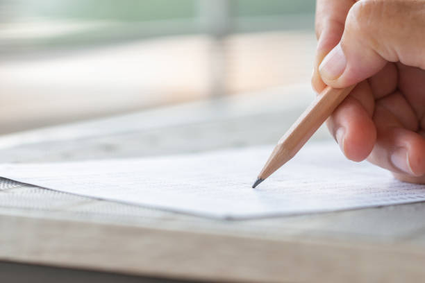 Student hand testing doing test exam with pencil drawing selected choices on answer sheet in school final exams at college or university. Taking multiple choice for assessment in examination classroom stock photo
