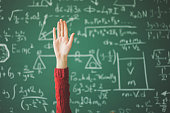 istock Student hand up behind green chalk board 944042668