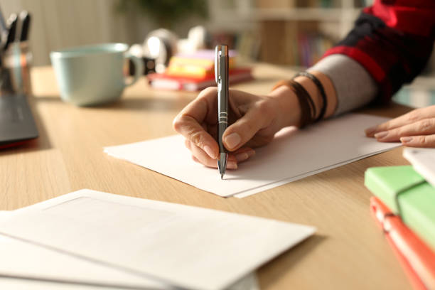 Student hand writing letter at home in the night Student hand writing letter at home in the night enrollment stock pictures, royalty-free photos & images