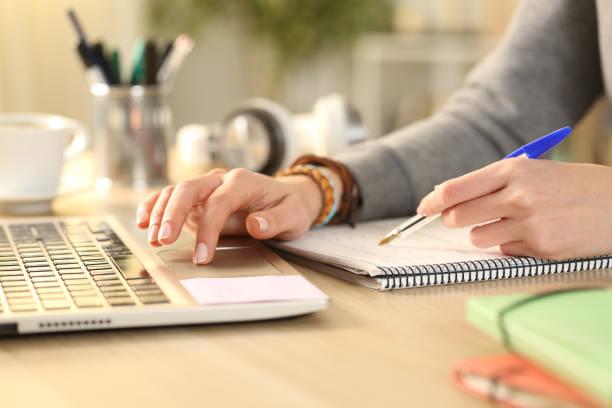 студенческие руки, сравнивая заметки на ноутбуке с ноутбуком - писать стоковые фото и изображения
