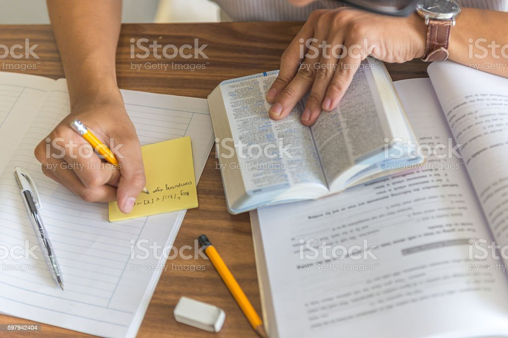 Student hands taking note and looking up dictionary while studying foto royalty-free