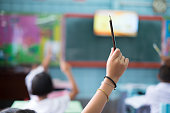 istock Student hands up asking a question in class at the elementary school. Education concept. 1158216572
