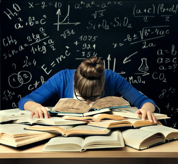 student hard study, tired bored woman read books over blackboard math formulas, difficult education - esame maturità foto e immagini stock
