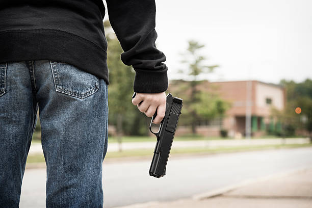 Student Holding a Gun Outside of School A student wearing jeans and a black hoodie stands outside of school holding a gun.Similar Images: mass murder stock pictures, royalty-free photos & images