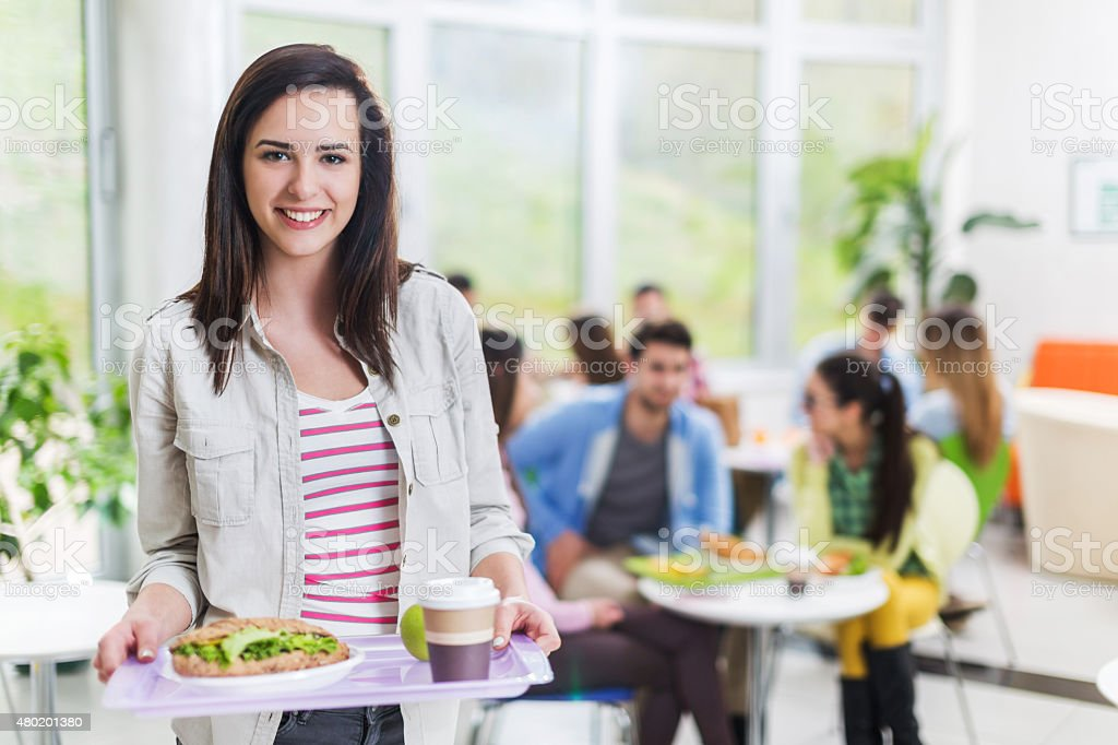 Student holding a tray in cafeteria and looking at camera. stock photo