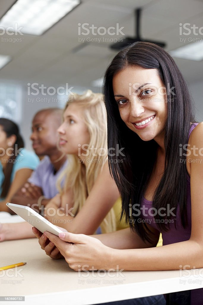 Student holding portable screen while sitting with her friends royalty-free stock photo