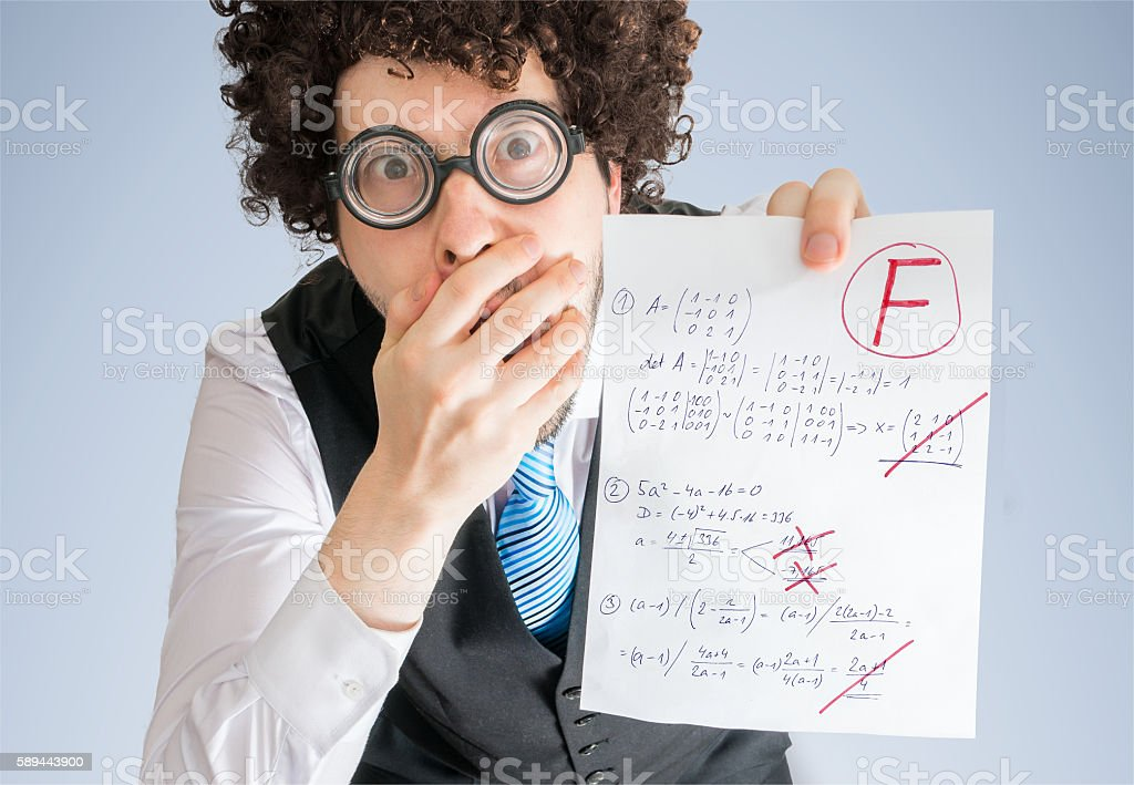 Student holds math exam and is disappointed from F grade. stock photo
