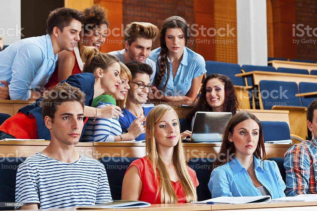 Large group of high school students sitting in the lecture hall at...
