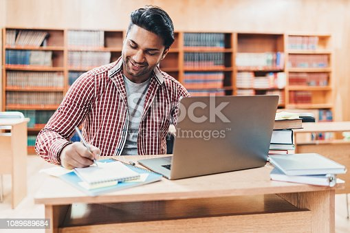 Indian ethnicity student working in a public library