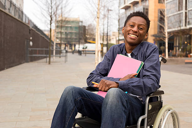 student in a wheelchair a young student in a wheelchair male likeness stock pictures, royalty-free photos & images