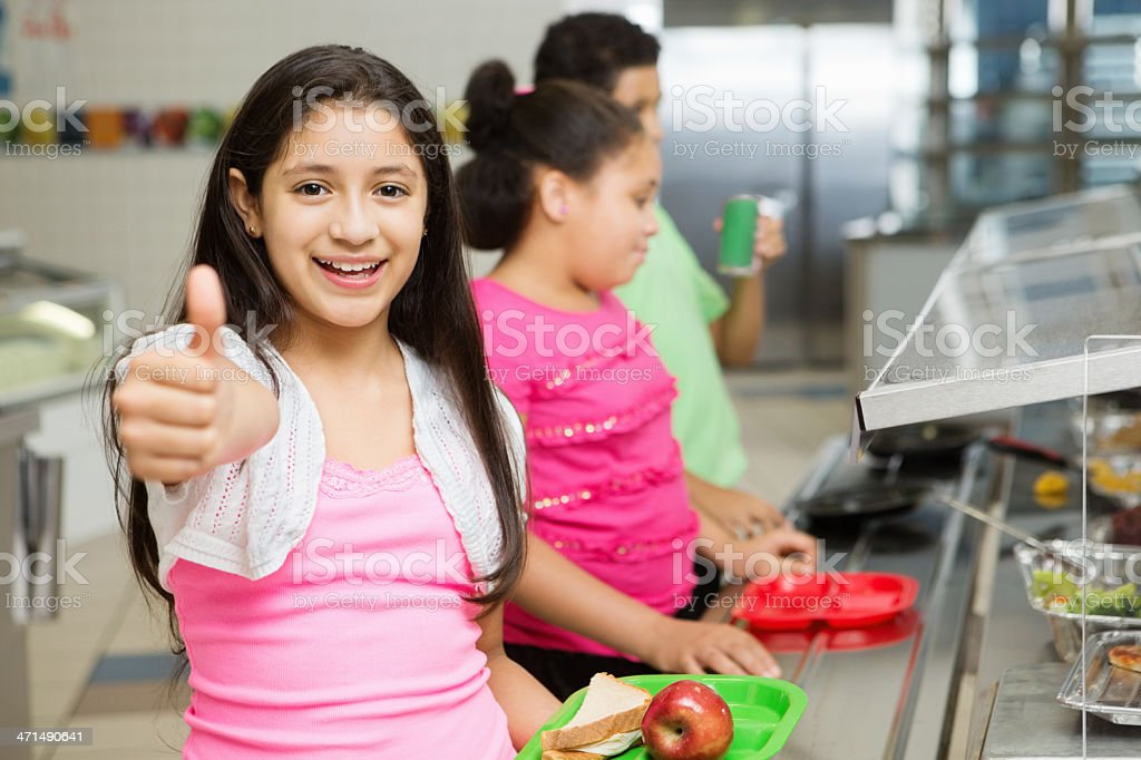 Student in cafeteria giving ''thumbs up'' making healthy lunch choices royalty-free stock photo