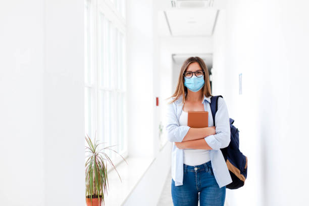 Student in protective face mask in empty college indoors. Young woman going to exams in high school. stock photo